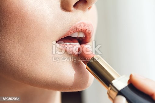 istock Beauty photo of applying lipstick 850892934