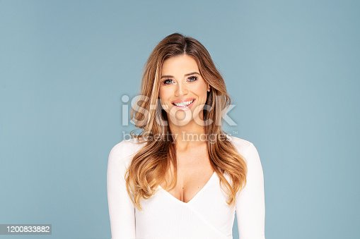 Beauty photo of female face with healthy natural long wavy hair and delicate makeup.Pretty attractive young woman posing at studio on blue studio background.