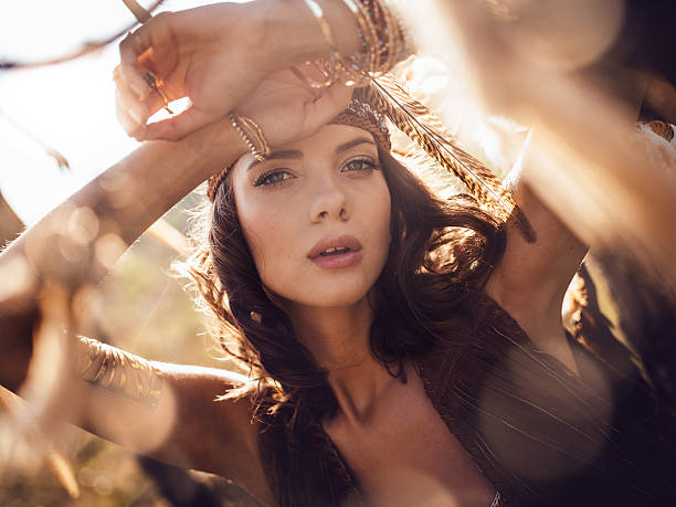 Beauty portrait of a boho girl in afternoon sunlight Closeup beauty portrait of a wild looking boho girl gazing at the camera in golden afternoon sunlight romani people stock pictures, royalty-free photos & images