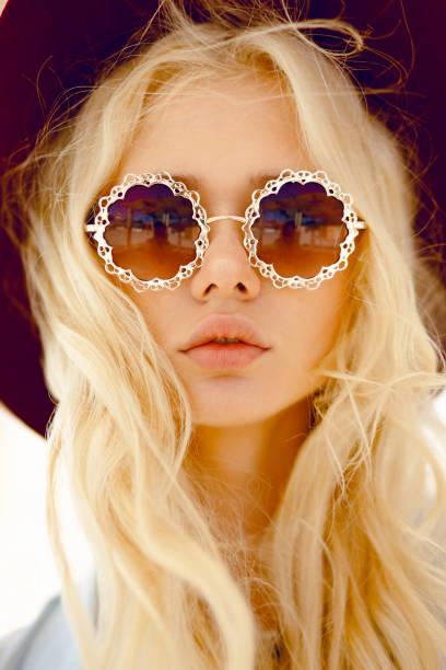beauty-porträt einer sexy blondine mit runden blumenbrillen, großen lippen, gewellten haaren und burgunder hut, mit blick auf kamera. - haarschnitt rundes gesicht stock-fotos und bilder