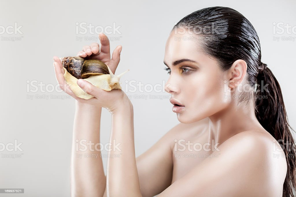 Beauty portrait of a young woman holding snail royalty-free stock photo