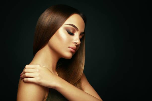verticale de beauté d'une jeune femme avec le long cheveu droit et le beau maquillage dans le studio sur un fond foncé - cheveux lisses photos et images de collection