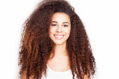 Beauty portrait of young attractive african american girl with toothy smile. Long curly hair. Girl looking at camera. White background.