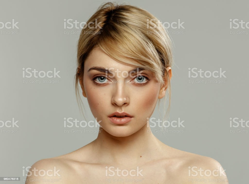 Young female face with natural skin texture isolated on grey