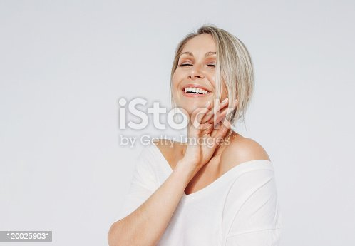 istock Beauty portrait of blonde smiling laughing woman 35 year plus clean fresh face with close eyes isolated on white background 1200259031