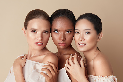 Beauty. Portrait Of Diversity Models. Mixed Race, Asian And Caucasian Girls Hugs Each Other And Looking At Camera. Different Ethnicity Women With Nude Makeup And Perfect Glowing Skin.