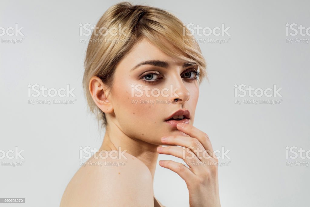 Photo of young woman face touching her lips, isolated on grey...