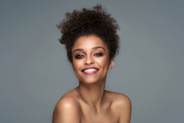 Beauty portrait of smiling dark skin young woman. Beauty portrait of smiling dark skin young woman with curly afro hair and glamour makeup. Studio  shot on gray background, copy space. dark skin stock pictures, royalty-free photos & images