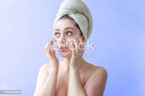 istock Beauty portrait of woman in towel on head with white nourishing mask or creme on face, blue background isolated 1136194304