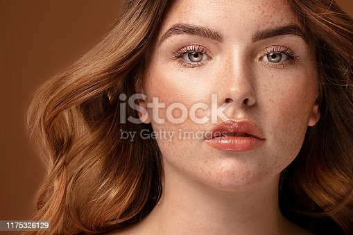 Beauty portrait od delicate caucasian lady. Beautiful ginger woman with long hair and with freckles posing on brown studio background.