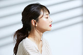 光と影の背景に若いアジアの女性の美の肖像画