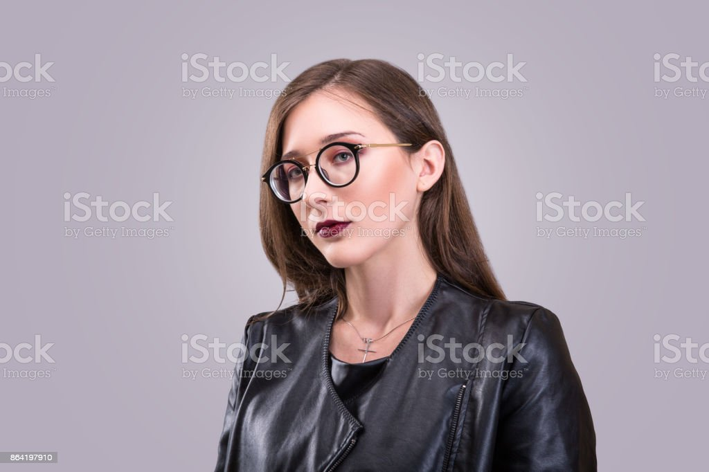 Beauty portrait of young attractive woman wearing glasses with agressive make-up dressed in laither jacket royalty-free stock photo