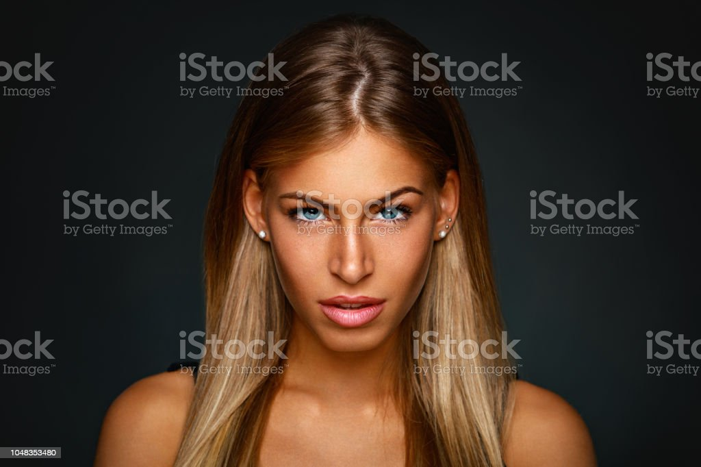 Beauty portrait of young blonde in a studio on a dark background stock photo