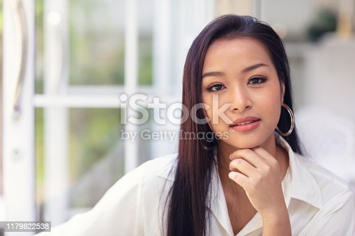 Portrait of an attractive asian woman in makeup looking at the camera.