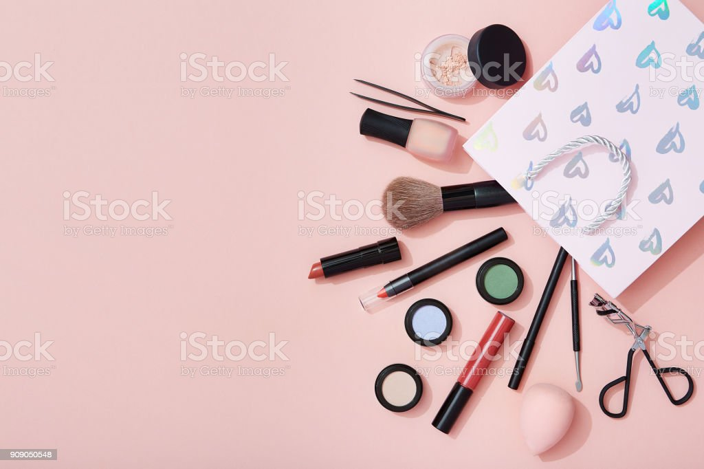 Beauty products and a gift bag flat lay on pink background