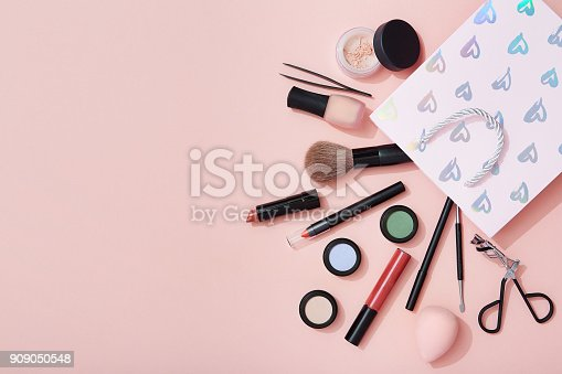 istock Beauty products and a gift bag flat lay on pink background 909050548