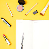 istock Beauty products and open blank note book flat lay on pastel background 869040880
