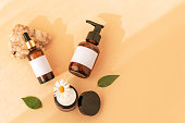 istock Beauty products: wash gel, cream jar, serum on natural stone, yellow background, top view 1249001239