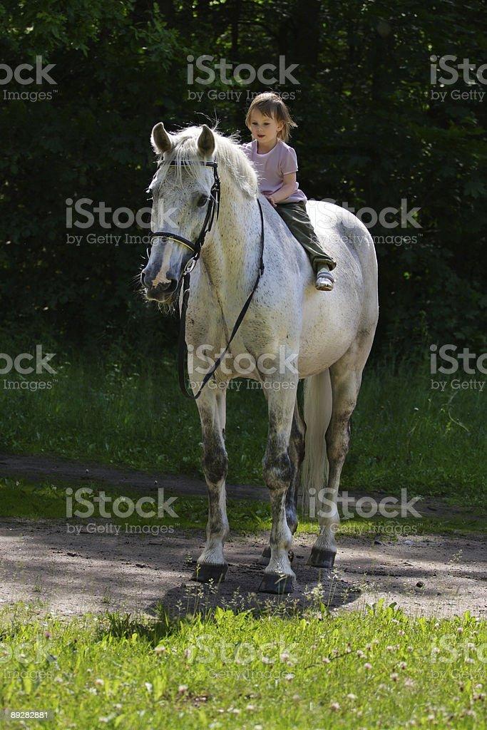Beauty satisfied girl riding bareback by gray horse royalty-free stock photo