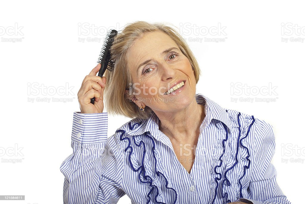 Beauty senior woman brushing hair stock photo