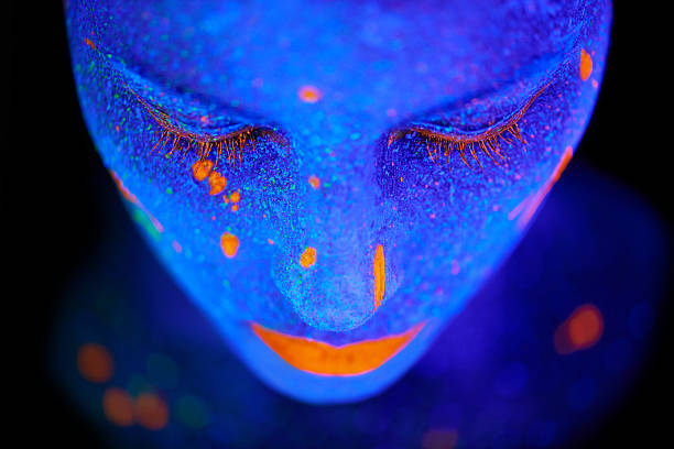 Beauty shines brightest in the dark Shot of a young  woman posing with neon paint on her face body paint stock pictures, royalty-free photos & images