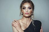 istock Beauty shooting with brunete model. Editorial studio gray bakground 1252385089