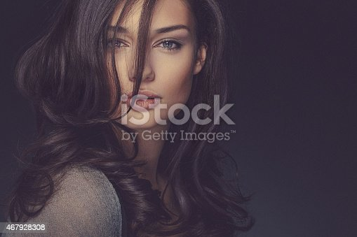 A close-up beauty portrait of a smiling young confident woman looking straight at the camera. The woman has blue eyes and long dark curly hair that lighly covers half of her face. The woman's shoulder is visible and covered with a neutral gray fabric. She is isolated on a dark background. Developed from RAW; retouched with special care and attention; small amount of grain added for best final impression; ready made for print and web use;