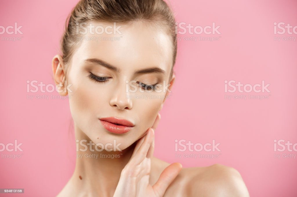 Beauty skin Concept - Beautiful Young Caucasian Woman with Clean Fresh Skin look away with pink studio background. Girl beauty face care. Facial treatment. Cosmetology , beauty and spa. stock photo
