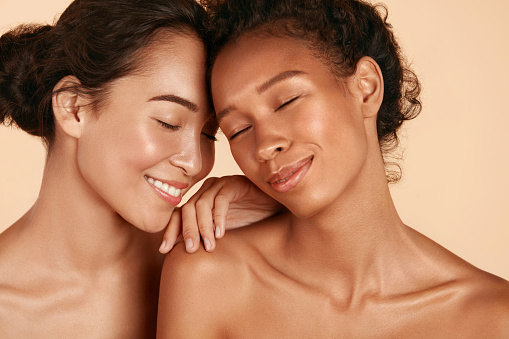 Beauty. Smiling women with perfect face skin and natural makeup portrait. Beautiful happy asian and african girl models with different types of skin on beige background. Spa skin care concept