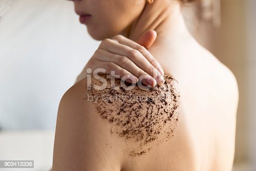 istock Beauty, spa and healthy skin concept - woman cleans skin of the body with coffee scrub in bathroom. 903413336