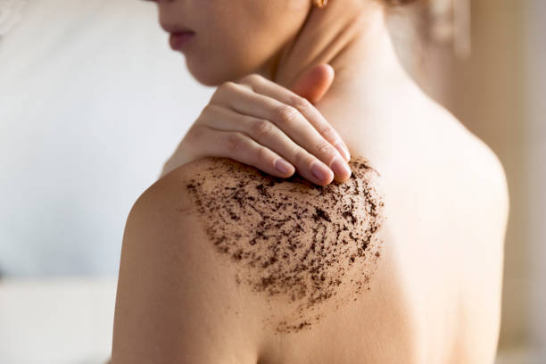 Beauty, spa and healthy skin concept - woman cleans skin of the body with coffee scrub in bathroom. stock photo