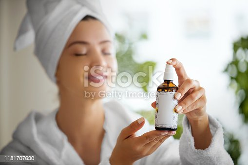 Young woman applying oxygen on her face with her eyes closed. Focus on product.