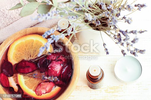 istock Beauty spa treatment with essential oils, bowl of water with orange fruit citrus pieces and flower petals 1219757089