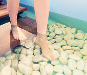 A woman walking over rounded pebbles during treatment at a beauty spa.