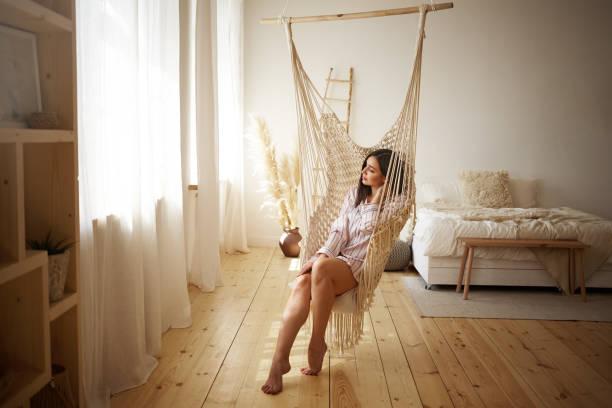 schoonheid, stijl, rust en ontspanning concept. foto van modieuze jonge plus size vrouw genieten langzaam lui weekend ochtend thuis, zittend blote voeten in hangende stoel in lichte ruime slaapkamer - schommelen bungelen stockfoto's en -beelden