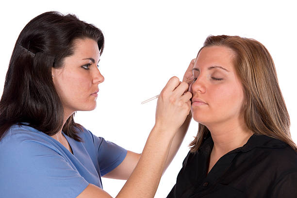 Beauty technician applying makeup on client stock photo