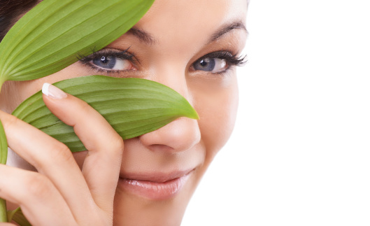 Closeup portrait of a woman looking at the camera through green leaves