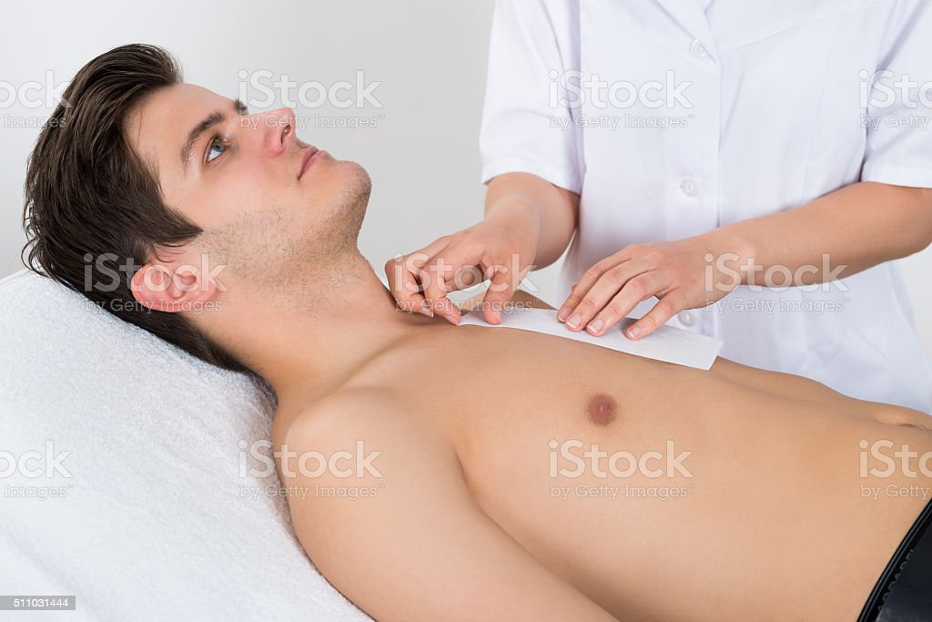 Beauty Therapist Waxing Man's Chest stock photo