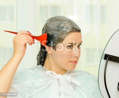 woman looking in the mirror and dying her hair.