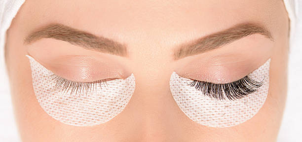 beauty treatment, application of false eyelashes front view of woman with eyes closed at spa salon, false eyelashes application. beauty treatment concept. false eyelash stock pictures, royalty-free photos & images