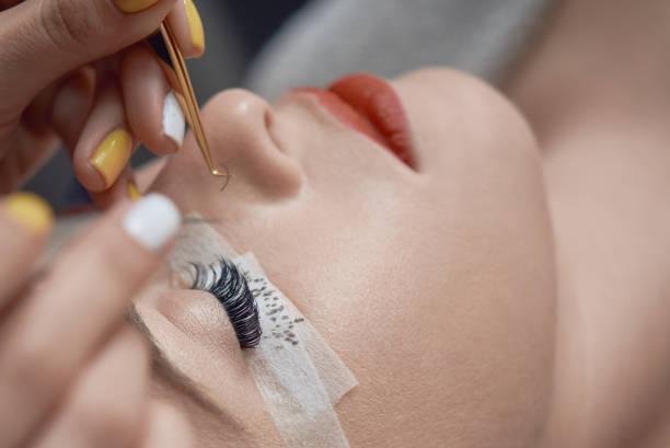 beauty treatment, applying false eyelashes beautician hands with working tools applying false eyelashes to her customer in spa salon, beauty treatment concept. false eyelash stock pictures, royalty-free photos & images
