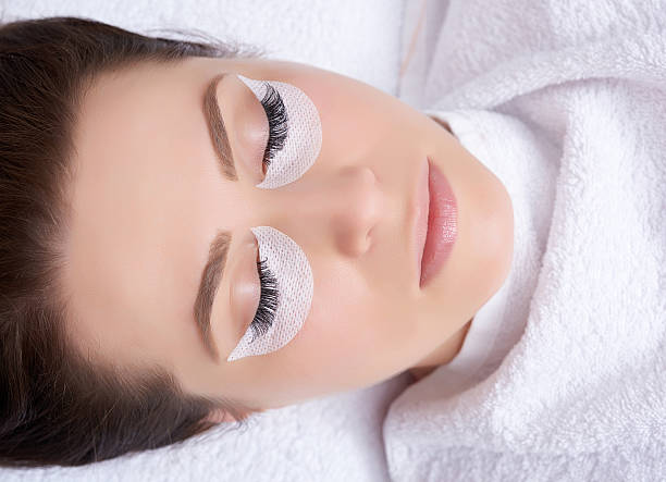 beauty treatment high angle view of young woman lying down in spa salon with her eyes closed and relaxing.false eyelashes extension. false eyelash stock pictures, royalty-free photos & images