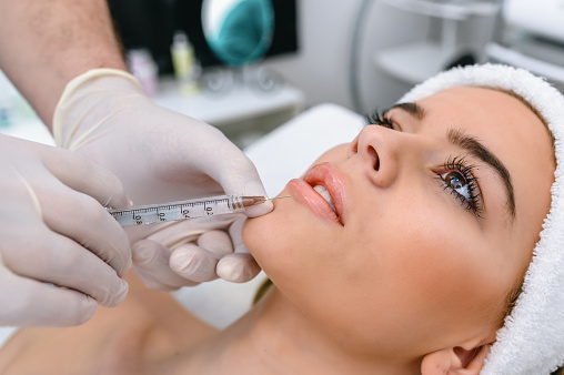 The doctor cosmetologist makes the Rejuvenating facial injections procedure for tightening and smoothing wrinkles on the face skin of a beautiful, young woman in a beauty salon. The hands of cosmetologist are close-ups that inject hyaluronic acid into the lips of the woman.