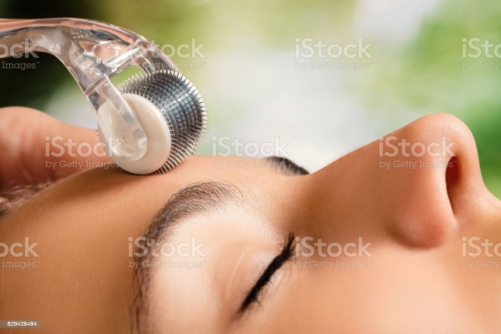Beauty treatment with skin derma roller. stock photo