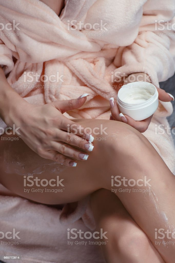 Beauty & Wellness Beauty 29 years woman applying body lotion on her legs. Sitting on the hardwood floor in bathrobe. stock photo