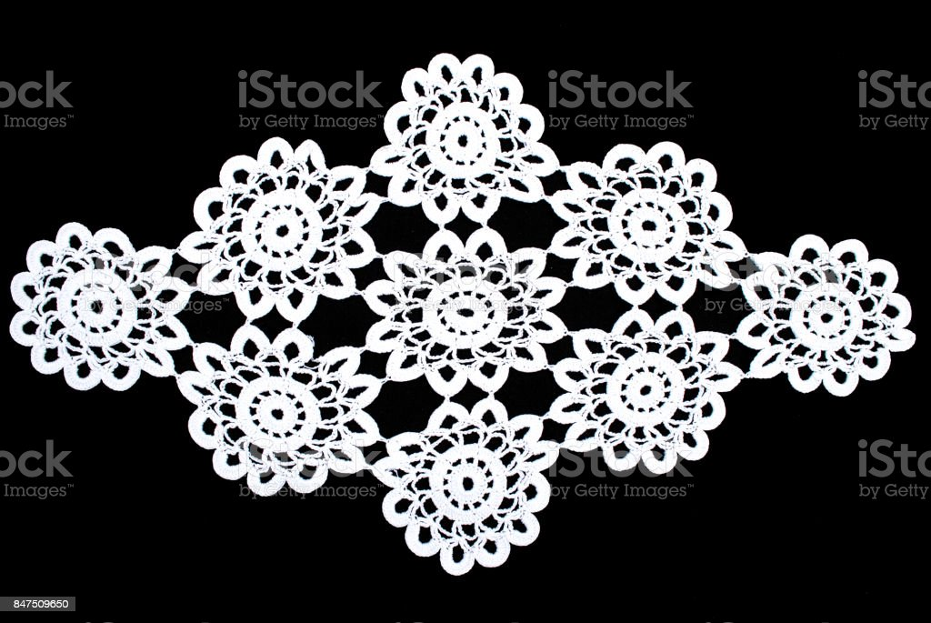 Beauty white lace tablecloth isolated on black background, floral pattern stock photo