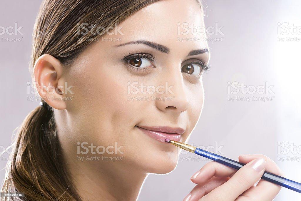 Beauty woman applying lipstick. stock photo