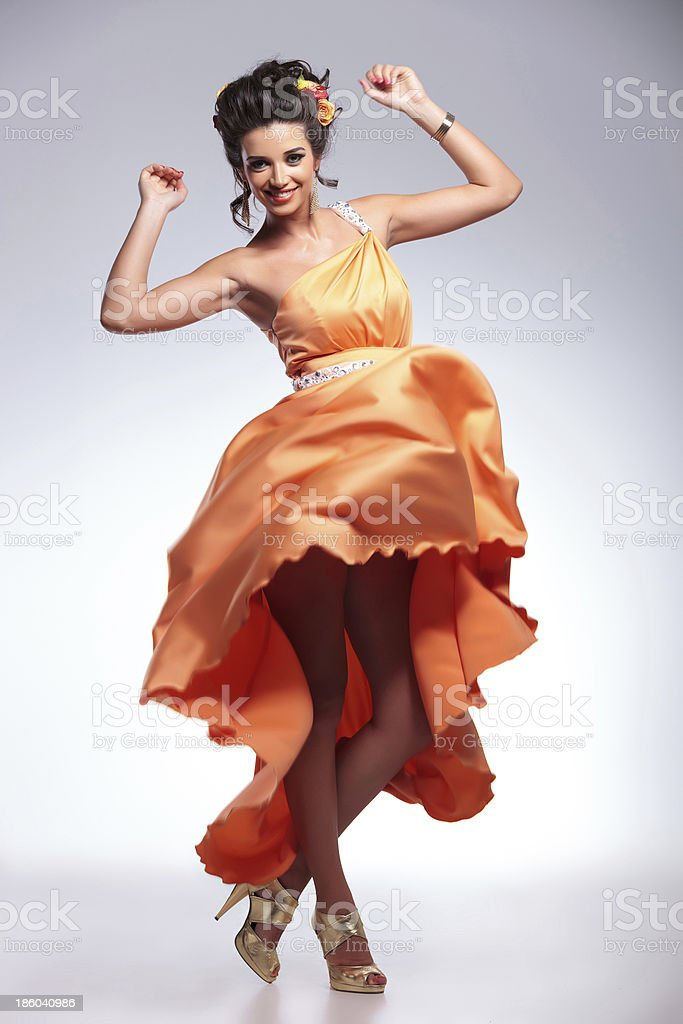 beauty woman dancing with her dress in the air stock photo