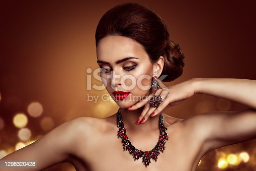 Beauty Woman Face Makeup and Jewelry, Fashion Model Portrait with Jewellery Ring Necklace Earrings over Lights Background