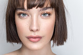 Close up studio shot of a beautiful girl with short brown hair, freckles and soft make up.